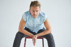 hombre-brutal-en-una-camisa-con-las-mangas-cortas-que-se-sientan-en-una-silla-roja-68233180